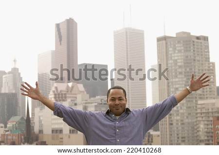 African man with arms out standing in front of cityscape - stock photo