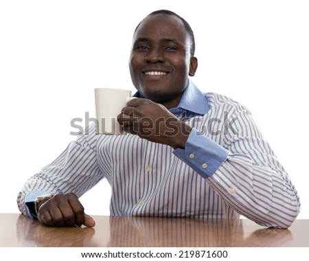 African man with cup of tea, sitting on the desk - stock photo