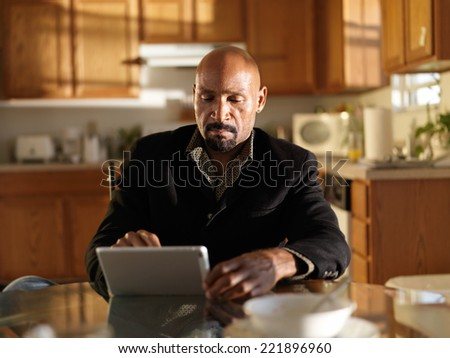 african man with tablet in early morning inside kitchen - stock photo