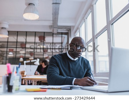 African man writing notes while working on a laptop in an modern office. Busy young man working at his desk. - stock photo