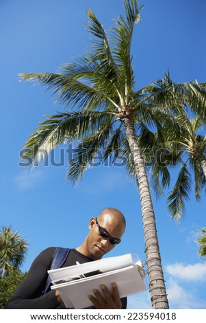 African man writing on clipboard - stock photo