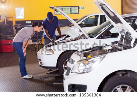 african mechanic and female customer in front her car with bonnet open - stock photo