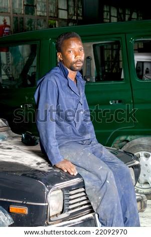 african mechanic resting in garage during lunch break - stock photo