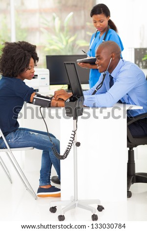 african medical doctor measuring patient's blood pressure in office - stock photo