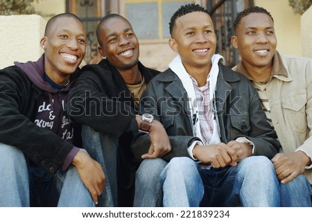 African men sitting on porch steps - stock photo