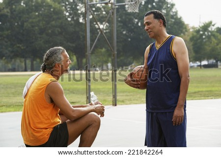 African men talking on basketball court - stock photo