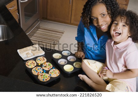 African mother and daughter making cupcakes - stock photo