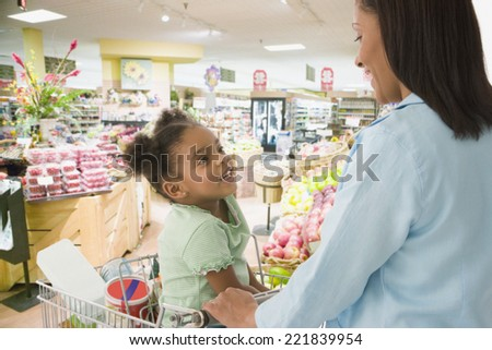 African mother and daughter shopping in grocery store - stock photo