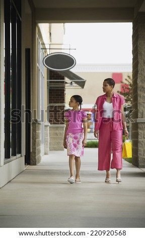 African mother and daughter window shopping - stock photo