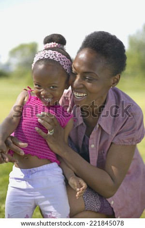 African mother hugging daughter