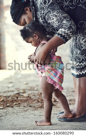 African mother teaching baby to walk in rural setting - stock photo