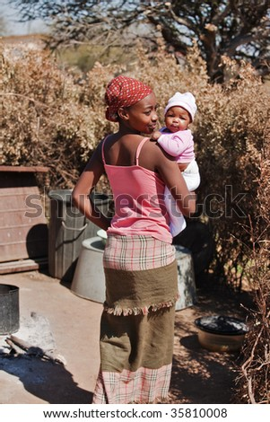 African mother with baby girl, going to the summer kitchen, location Mmankgodi village , Botswana