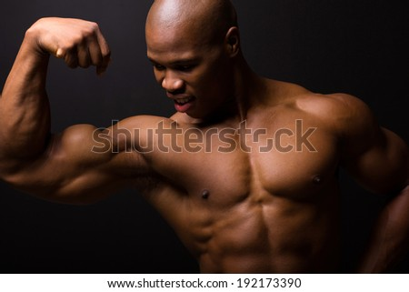 african muscular bodybuilder on black background - stock photo