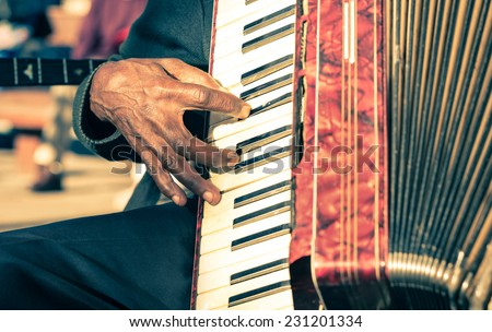 African musician hand playing fisarmonica - Street artist performing traditional songs with accordion  - stock photo