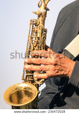 African musician hand playing music with trumpet - Street artist performing traditional soul jazz songs - stock photo