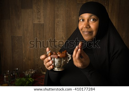 African muslim woman in black veil presenting traditional sweet dates - stock photo