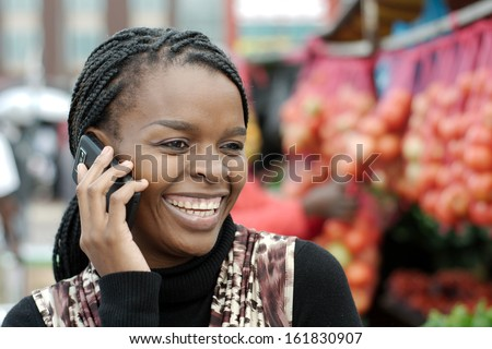 African or black American woman calling on mobile cellphone telephone in Alexandra township