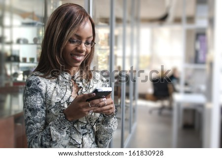 African or black American woman calling or texting on mobile cellphone telephone in office - stock photo