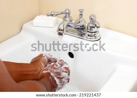African person washing hands with soapy water