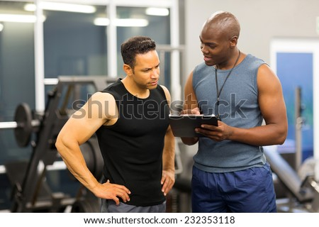 african personal trainer helping man to fill the membership form of health club - stock photo