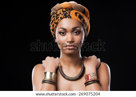 African queen. Beautiful African woman wearing a headscarf and touching her shoulders while standing against black background - stock photo
