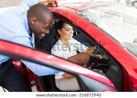 african salesman showing a new car to beautiful young woman - stock photo