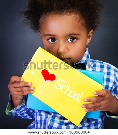 African schoolboy portrait, cute little child with holding book with text: i love school, on blackboard background, for the first time in first class - stock photo