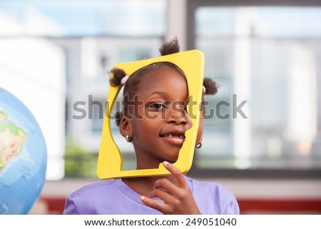 African schoolgirl joking with object in primary classroom.