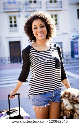 African student holding a trolley case and a jacket on urban background - stock photo