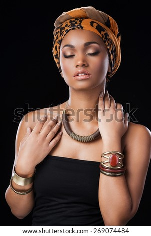 African style. Beautiful African woman wearing a headscarf and keeping eyes closed while standing against black background - stock photo