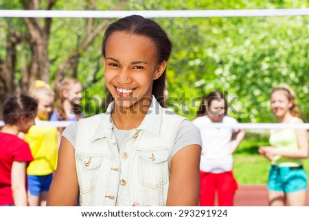 African teen girl and friends playing volleyball - stock photo