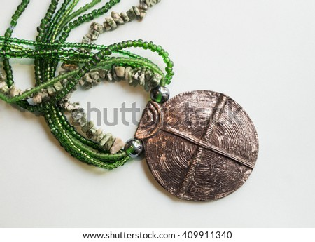 African traditional ethnic beads, natural stones jewelry necklace with metal buckle isolated on white background. Green tint. Modern fashion art tribal accessories. - stock photo