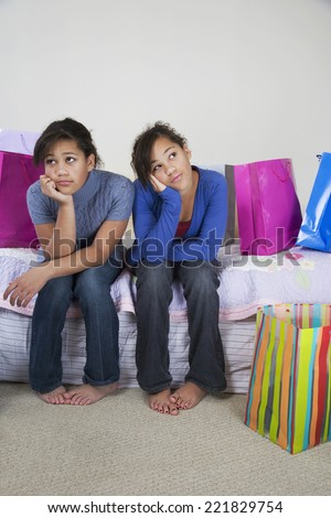 African twin sisters looking bored - stock photo