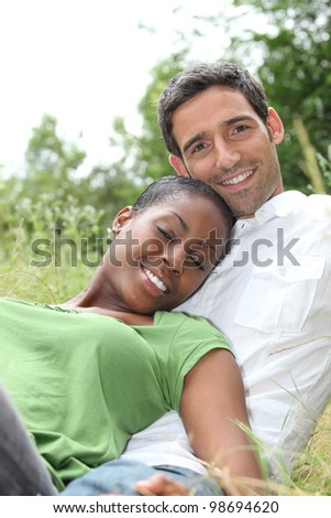 African woman and white man hugging - stock photo