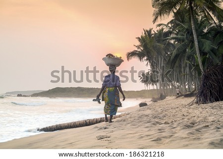 African woman at beautiful sunset on a paradise beach, West Africa - stock photo