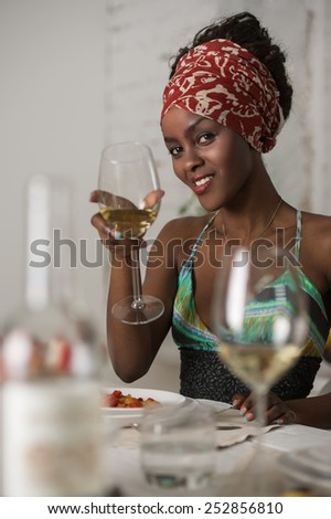 African woman eating at home and drinking wine and looking very happy - stock photo
