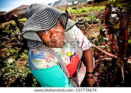 african woman happily gardening on a sunny day  wearing a sunhat and apron