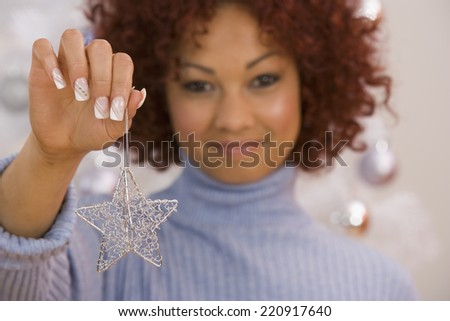 African woman holding Christmas ornament - stock photo