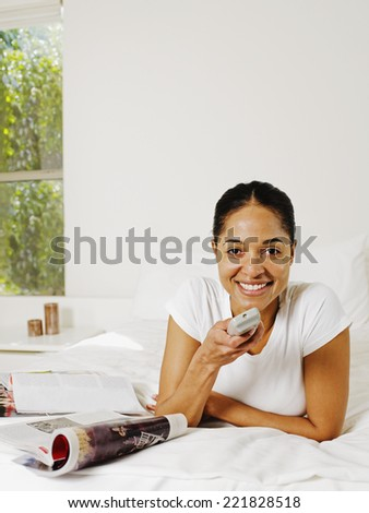 African woman holding remote control - stock photo