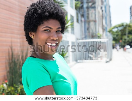 African woman in a green shirt in the city with buildings and street in the background