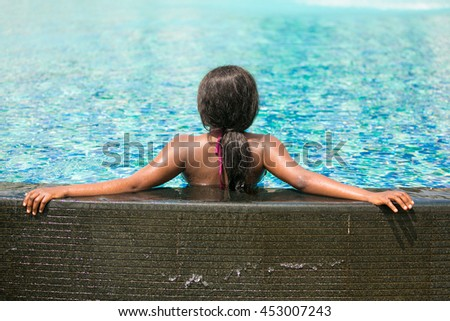 African woman in the swimming pool during summer vacation.
