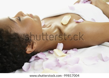 African woman laying on spa table - stock photo