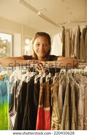 African woman leaning on rack at clothing store - stock photo