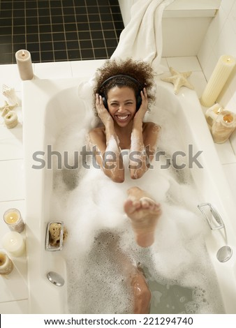 African woman listening to music in bath - stock photo