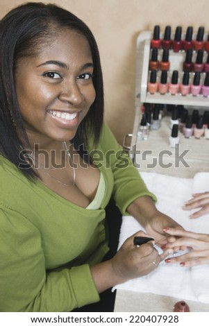 African woman performing manicure - stock photo