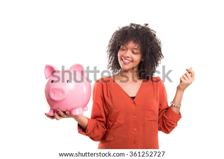 African woman putting some money into a piggy bank