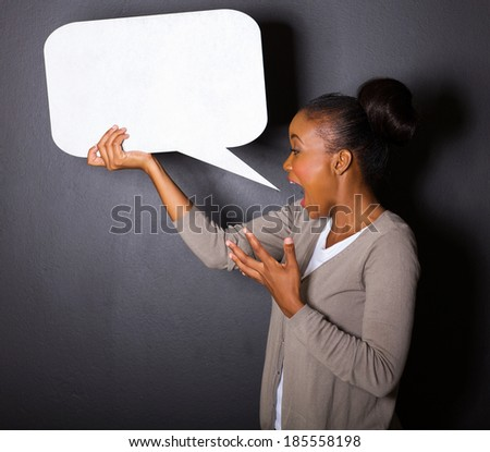 african woman screaming in blank speech bubble isolated on black background - stock photo