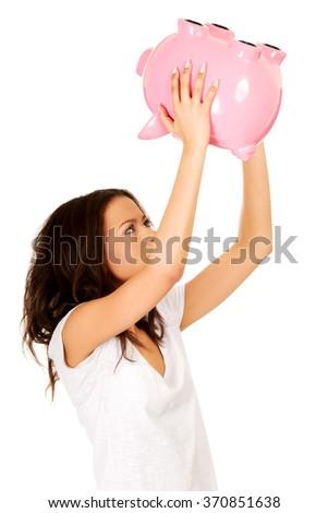 African woman shaking piggybank. - stock photo