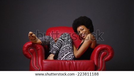 African woman sitting in red armchair - stock photo