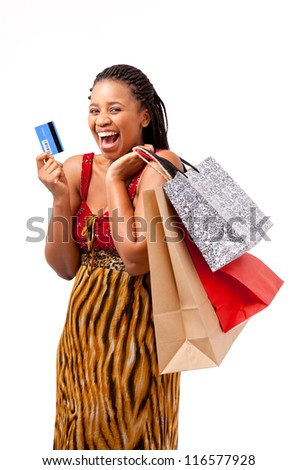 African woman smiling holding shopping bags and a blank card on an isolated background - stock photo
